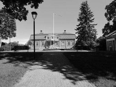 Fullersta Gård - fasad och gårdsplan i gråskala.